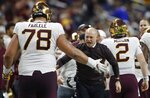 FILE - Minnesota head coach P.J. Fleck greets offensive lineman Daniel Faalele (78) after a play during the Quick Lane Bowl NCAA college football game against Georgia Tech in Detroit, in this Wednesday, Dec. 26, 2018, file photo. This mammoth lineman – he's 6-foot-9 and 380 pounds – was Minnesota's starting right tackle in 2018 and 2018. He should step right back into that role this year after sitting out the 2020 season. (AP Photo/Carlos Osorio, File)