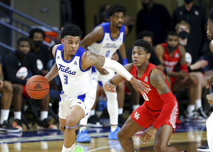 Tulsa's Elijah Joiner is defended by Houston's Marcus Sasser during the second half of an NCAA college basketball game in Tulsa, Okla., Tuesday, Dec. 29, 2020. Tulsa won 65-64. (AP Photo/Dave Crenshaw)