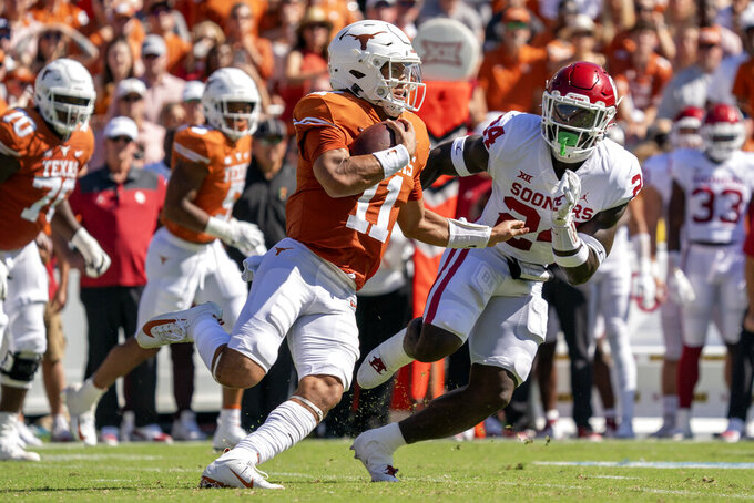 Texas quarterback Casey Thompson (11) turns upfield past Oklahoma linebacker Brian Asamoah (24) during the first half of an NCAA college football game at the Cotton Bowl, Saturday, Oct. 9, 2021, in Dallas. (AP Photo/Jeffrey McWhorter)