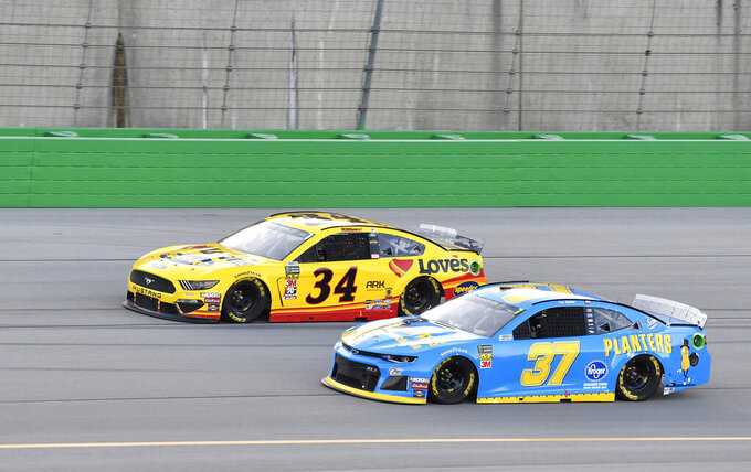Chris Buescher (37) takes the bottom of the track to try to pass Michael McDowell (34) during the NASCAR Cup Series auto race at Kentucky Speedway in Sparta, Ky., Saturday, July 13, 2019. (AP Photo/Timothy D. Easley)