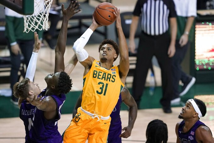 Baylor guard MaCio Teague (31) takes a shot over Stephen F. Austin's Nana Antwi-Boasiako, left front, David Kachelrie, left rear, and DeAndre Heckard, right, in the second half of an NCAA college basketball game in Waco, Texas, Wednesday, Dec. 9, 2020. (AP Photo/Tony Gutierrez)