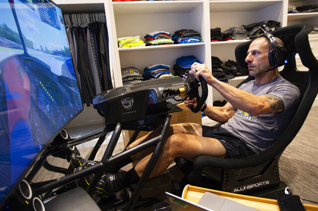 IndyCar driver Tony Kanaan, of Brazil, practices on his racing simulator in his home in Indianapolis, Saturday, March 28, 2020. Kanaan, along with other IndyCar drivers and NASCAR's Jimmie Johnson will compete in the series' inaugural virtual racing event Saturday. (AP Photo/Michael Conroy)