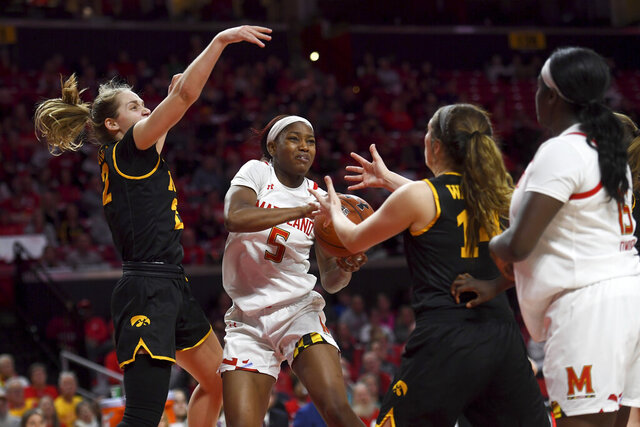 Maryland guard Kaila Charles (5) looks to score despite pressure from Iowa guards Kathleen Doyle (22) and Mckenna Warnock (14) in the third period of an NCAA college basketball game Thursday, Feb. 13, 2020, in College Park, Md. (Katherine Frey/The Washington Post via AP)