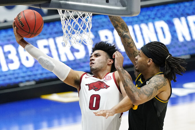 Arkansas' Justin Smith (0) drives against Missouri's Mitchell Smith, right, in the first half of an NCAA college basketball game in the Southeastern Conference Tournament Friday, March 12, 2021, in Nashville, Tenn. (AP Photo/Mark Humphrey)