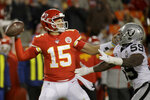 Kansas City Chiefs quarterback Patrick Mahomes (15) holds off Oakland Raiders linebacker Tahir Whitehead (59) during the second half of an NFL football game in Kansas City, Mo., Sunday, Dec. 1, 2019. (AP Photo/Charlie Riedel)