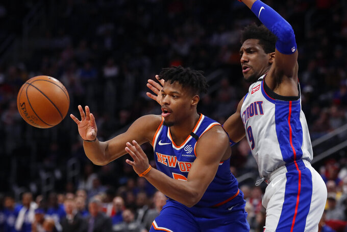 New York Knicks guard Dennis Smith Jr. passes as Detroit Pistons guard Langston Galloway (9) defends during the first half of an NBA basketball game, Saturday, Feb. 8, 2020, in Detroit. (AP Photo/Carlos Osorio)
