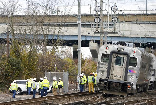 Emergency personnel talk near a derailed train in Perth Amboy, N.J., Tuesday, Nov. 24, 2020. Multiple cars of a New York City-bound commuter train derailed early Tuesday, leading to delays during the morning rush hour. No injuries were reported. (AP Photo/Seth Wenig)
