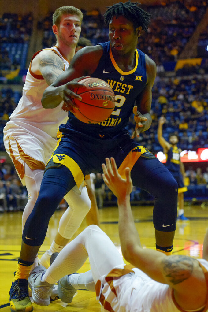 West Virginia forward Andrew Gordon (12) tries to maneuver during the second half of an NCAA college basketball game against Texas in Morgantown, W.Va., Saturday, Feb. 9, 2019. (AP Photo/Craig Hudson)