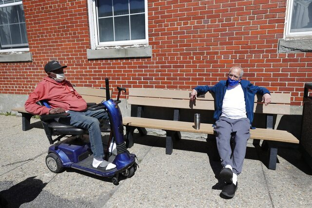 Air Force veteran Willie Williams, 63, left, chats with Army veteran Vincent Whittemore outside the Soldiers' Home, Monday, April 6, 2020, in Chelsea, Mass. U.S. Secretary of Veterans Affairs Robert Wilkie said Sunday the federal Department of Veterans Affairs will provide the assistance at the Chelsea Soldier's Home and the Holyoke Soldiers' Home that have been hard-hit in the coronavirus pandemic. (AP Photo/Elise Amendola)