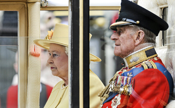 FILE - In this April 29, 2011 file photo, Britain's Prince Phillip sits beside Queen Elizabeth II in a carriage leaving Westminster Abbey after the Royal Wedding of Prince William and Kate Middleton in London. Prince Philip, the irascible and tough-minded husband of Queen Elizabeth II who spent more than seven decades supporting his wife in a role that both defined and constricted his life, has died, Buckingham Palace said Friday. He was 99. (AP Photo/Martin Meissner, File)