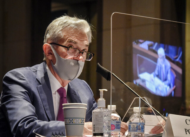 FILE - In this June 30, 2020, file photo Federal Reserve Board Chairman Jerome Powell, reflected in the sneeze guard set up between himself and members of the House Committee on Financial Services, speaks during a hearing on oversight of the Treasury Department and Federal Reserve pandemic response on Capitol Hill in Washington. With the economy still in the pandemic's grip, the Federal Reserve is facing a decision on whether to stretch an emergency lending program in a way that could bring more risk for the government and taxpayers. Lawmakers are pressing the central bank to deliver more aid to struggling small and mid-sized businesses. (Bill O'Leary/The Washington Post via AP, Pool)