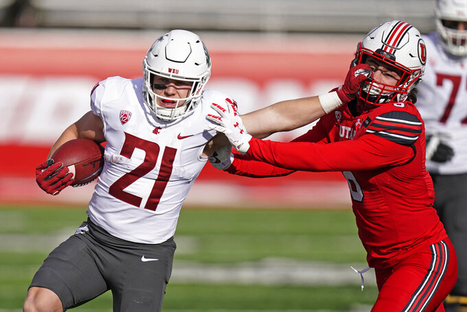 Utah safety Nate Ritchie, right, reaches to tackle Washington State running back Max Borghi (21) during the first half of an NCAA college football game Saturday, Dec. 19, 2020, in Salt Lake City. (AP Photo/Rick Bowmer)