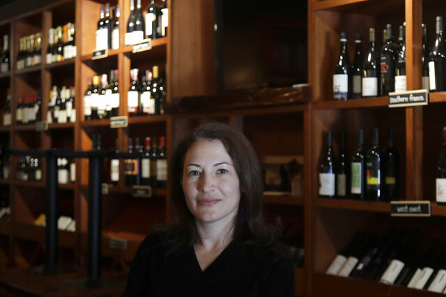 """Sarah Trubnick, owner of The Barrel Room, poses for photos while interviewed at the restaurant during the coronavirus pandemic in San Francisco, Tuesday, July 14, 2020.  The Barrel Room, a San Francisco wine bar and restaurant, cautiously reopened this month, hoping to salvage as much of 2020 as possible.  But as infections climb, Trubnick isn't taking anything for granted. """"We are prepared at any minute to close again,'' she said. """"It's a very stressful situation.'' (AP Photo/Jeff Chiu)"""