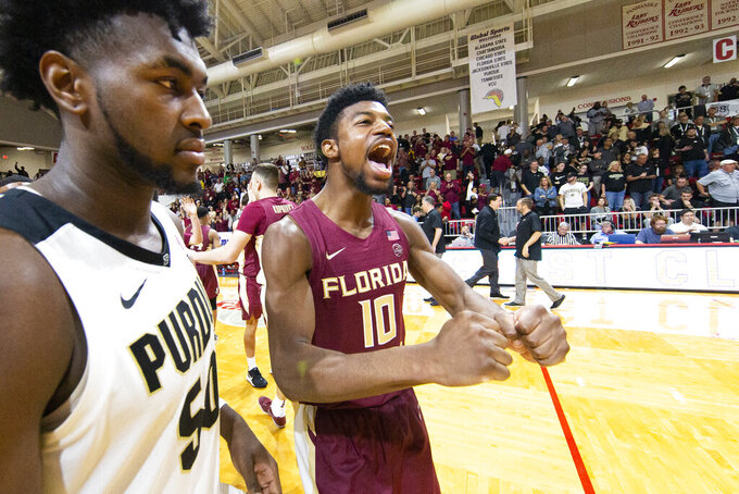 As Purdue forward Trevion Williams (50) heads to the dressing room, Florida State forward Malik Osborne (10) celebrates the 63-60 victory over Purdue in overtime of an NCAA college basketball game at the Emerald Coast Classic in Niceville, Fla., Saturday, Nov. 30, 2019. (AP Photo/Mark Wallheiser)