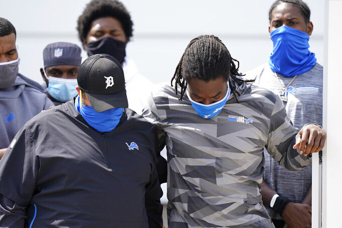 Detroit Lions head coach Matt Patricia, left, and a player listen as defensive end Trey Flowers (not shown) addresses the media with his teammates outside the Lions NFL football camp practice facility, Tuesday, Aug. 25, 2020, in Allen Park, Mich. The players were reacting to the recent shooting of Jacob Blake in Kenosha, Wis., on Sunday. (AP Photo/Carlos Osorio)
