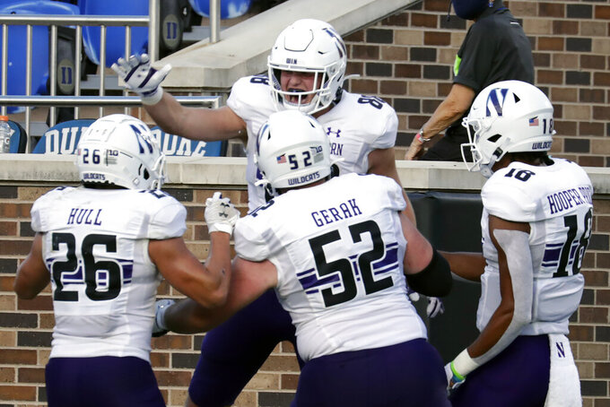 Northwestern tight end Marshall Lang (88) celebrates his touchdown reception with running back Evan Hull (26), offensive lineman Sam Gerak (52) and wide receiver Genson Hooper Price (18) during the second half of an NCAA college football game against Duke in Durham, N.C., Saturday, Sept. 18, 2021. (AP Photo/Chris Seward)