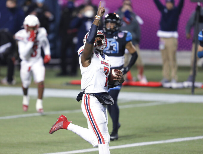 Liberty quarterback Malik Willis (7) celebrates after scoring a touchdown against Coastal Carolina during the first half of the Cure Bowl NCAA college football game Saturday, Dec. 26, 2020, in Orlando, Fla. (AP Photo/Matt Stamey)
