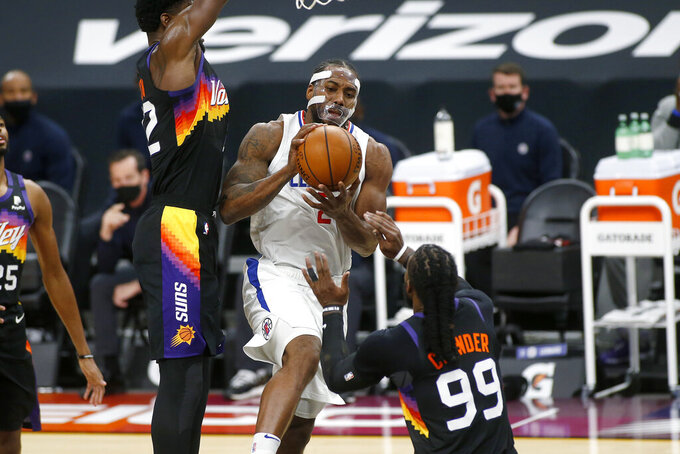 Los Angeles Clippers forward Kawhi Leonard (2) drives to the basket between the defense of Phoenix Suns center Deandre Ayton, left, and forward Jae Crowder (99) during the first half of an NBA basketball game Sunday, Jan. 3, 2021, in Phoenix. (AP Photo/Ralph Freso)