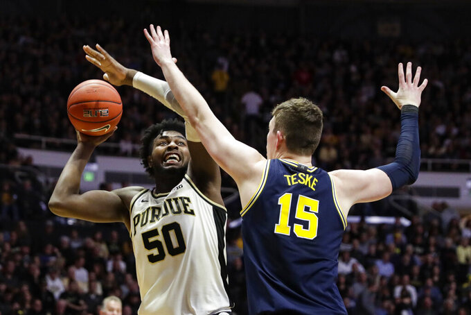 FILE - Purdue forward Trevion Williams (50) shoots over Michigan center Jon Teske (15) during the second half of an NCAA college basketball game in West Lafayette, Ind., in this Feb. 22, 2020, file photo. Williams is sturdy and experienced enough to handle whatever comes his way. The 6-foot-9, 265-pound junior embraced the hefty workload he took on last season and thrived. This season, with a group of younger teammates in the mix, coach Matt Painter expects his big man to play an even more significant role.(AP Photo/Michael Conroy, File)