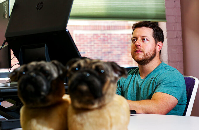 Cuddle Clones co-founder Adam Greene takes orders in his second-floor office on Baxter Ave. in Louisville, Ky. Co-founders Adam Green and Jennifer Williams have seen Cuddle Clones rocket to success since their start in 2013. (Jeff Faughender/Courier Journal via AP)