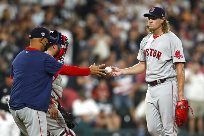 Boston Red Sox manager Alex Cora, left, takes the ball from relief pitcher Garrett Richards, right, during the fourth inning of a baseball game against the Chicago White Sox, Saturday, Sept. 11, 2021, in Chicago. (AP Photo/Jeff Haynes)