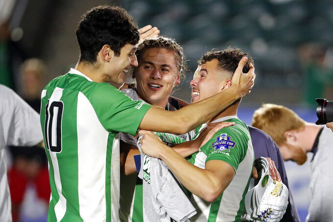 Marshall's Pedro Dolabella (10), Max Schneider, center, and Jamil Roberts, right, celebrate following the team's 1-0 overtime win over Indiana at the NCAA College Cup championship soccer match in Cary, N.C., Monday, May 17, 2021. (AP Photo/Karl B DeBlaker)