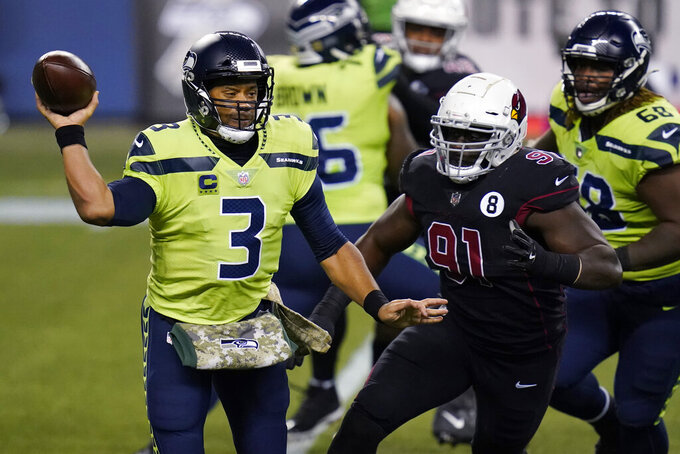 Seattle Seahawks quarterback Russell Wilson passes under pressure from Arizona Cardinals defensive end Michael Dogbe (91) during the first half of an NFL football game, Thursday, Nov. 19, 2020, in Seattle. (AP Photo/Elaine Thompson)