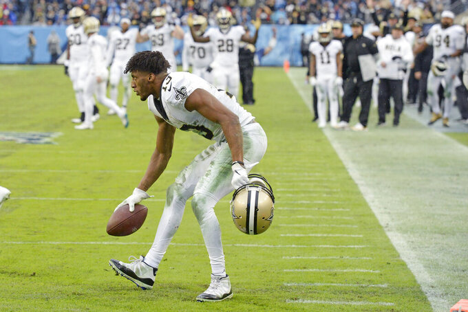 New Orleans Saints wide receiver Michael Thomas (13) picks up the ball after making a catch against the Tennessee Titans in the second half of an NFL football game Sunday, Dec. 22, 2019, in Nashville, Tenn. The catch gave Thomas the NFL single-season pass reception record. (AP Photo/Mark Zaleski)