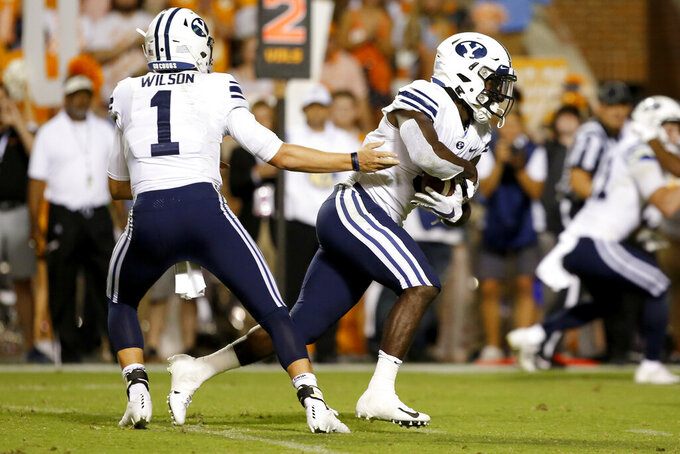 BYU quarterback Zach Wilson (1) hands the ball off to running back Ty'Son Williams (5) for what would be the game-winning 5-yard touchdown run during the second overtime against Tennessee in a NCAA football game at Neyland Stadium on Saturday, Sept. 7, 2019 in Knoxville, Tenn.(C.B. Schmelter/Chattanooga Times Free Press via AP)