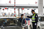 FILE - In this Jan. 23, 2020, file photo, a policeman uses a digital thermometer to take a driver's temperature at a checkpoint at a highway toll gate in Wuhan in central China's Hubei Province. Cutting off access to entire cities with millions of residents to stop a new virus outbreak is a step few countries other than China would consider, but it is made possible by the ruling Communist Party's extensive social controls and experience fighting the 2002-03 outbreak of SARS. (Chinatopix via AP)