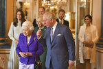 FILE - In this March 5, 2019 file photo, Britain's Queen Elizabeth II is joined by Prince Charles, the Prince of Wales, and at rear, from left, Kate, Duchess of Cambridge, Camilla, Duchess of Cornwall, Prince William, Prince Harry and Meghan, Duchess of Sussex during a reception at Buckingham Palace, London to mark the 50th anniversary of the investiture of the Prince of Wales. In a statement issued on Monday, Jan. 13, 2020, Queen Elizabeth II says she has agreed to grant Prince Harry and Meghan their wish for a more independent life that will see them move part-time to Canada.  (Dominic Lipinski/Pool via AP, File)