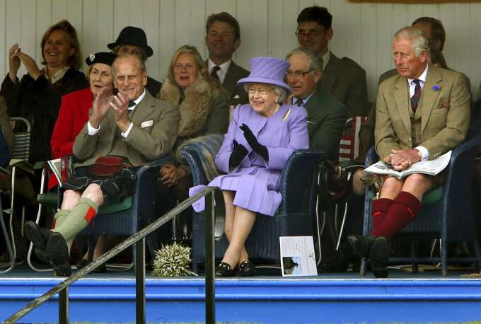 FILE - In this March 16, 2016 file photo, Britain's Queen Elizabeth II, Prince Philip and Prince Charles, right, attend the Braemar Royal Highland Gathering at the Princess Royal and Duke of Fife Memorial Park, Braemar, Scotland. Prince Philip, the irascible and tough-minded husband of Queen Elizabeth II who spent more than seven decades supporting his wife in a role that both defined and constricted his life, has died, Buckingham Palace said Friday, April 9, 2021. He was 99. (Andrew Milligan/PA via AP, File)