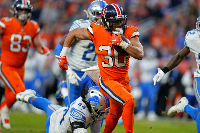 Denver Broncos running back Phillip Lindsay (30) breaks free from the grasp of Detroit Lions linebacker Jalen Reeves-Maybin (44) for a touchdown during the second half of an NFL football game, Sunday, Dec. 22, 2019, in Denver. (AP Photo/Jack Dempsey)