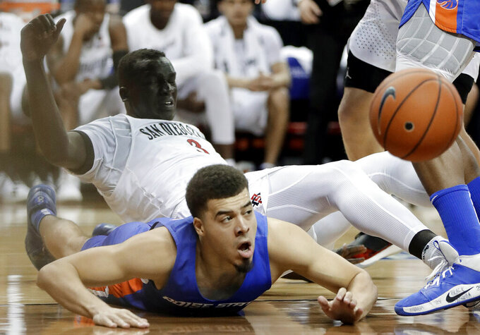 Boise State's Alex Hobbs (34) and San Diego State's Aguek Arop (3) go for a loose ball during the second half of an NCAA college basketball game in the Mountain West Conference men's tournament Friday, March 6, 2020, in Las Vegas. (AP Photo/Isaac Brekken)