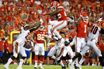 Kansas City Chiefs running back Darwin Thompson, center, is about to land on Cincinnati Bengals cornerback Darius Phillips, left, after trying to vault over  Bengals safety Brandon Wilson, right, a during the second half of an NFL preseason football game in Kansas City, Mo., Saturday, Aug. 10, 2019. (AP Photo/Ed Zurga)