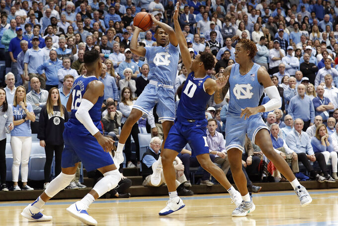 North Carolina guard Christian Keeling looks to pass while forward Armando Bacot, right, defends against Duke forward Javin DeLaurier (12) and forward Wendell Moore Jr. during the first half of an NCAA college basketball game in Chapel Hill, N.C., Saturday, Feb. 8, 2020. (AP Photo/Gerry Broome)