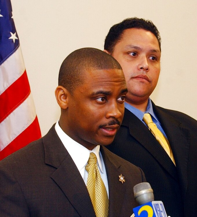 FILE - In this Jan. 11, 2005, file photo, Clayton County Sheriff Victor Hill, left, is flanked by a member of his legal team, attorney Rolf Jones, right, as he speaks during a news conference, in Jonesboro, Ga. The Atlanta-area sheriff, Hill, is accused of violating the civil rights of several people in his agency's custody by ordering that they be unnecessarily strapped into a restraint chair and left there for hours, according to a federal indictment. The indictment against Sheriff Hill was filed April 19, 2021, and was unsealed by a federal judge Monday, April 26. (AP Photo/Gene Blythe, File)