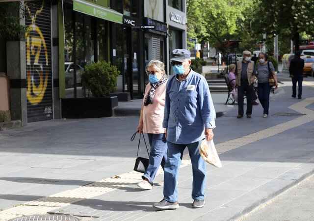 People wearing face masks for protection against coronavirus, walk in popular Tunali Hilmi Street during a four-day curfew declared by the government in an attempt to control the spread of coronavirus, in Ankara, Turkey, Sunday, May 17, 2020. Turkey's senior citizens were allowed to leave their homes for a second time as the country continues to ease some coronavirus restrictions. (AP Photo/Burhan Ozbilici)