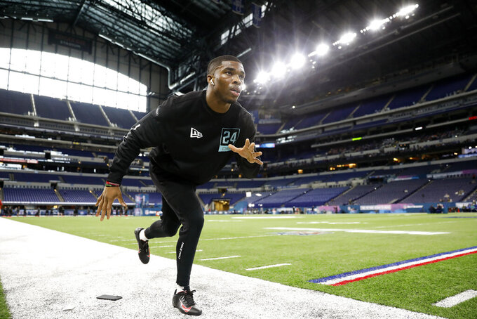 Ohio State defensive back Jeff Okudah stretches at the NFL football scouting combine in Indianapolis, Sunday, March 1, 2020. (AP Photo/Charlie Neibergall)