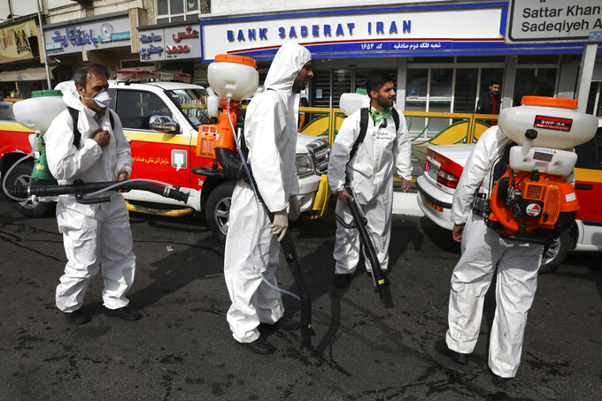 Firefighters prepare to disinfect a street against the new coronavirus, in western Tehran, Iran, Friday, March 13, 2020. The new coronavirus outbreak has reached Iran's top officials, with its senior vice president, Cabinet ministers, members of parliament, Revolutionary Guard members and Health Ministry officials among those infected.  The vast majority of people recover from the new coronavirus. According to the World Health Organization, most people recover in about two to six weeks, depending on the severity of the illness. (AP Photo/Vahid Salemi)