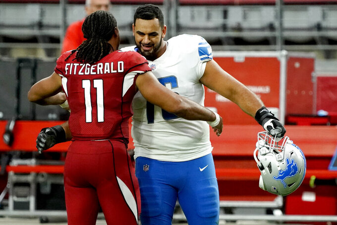 FILE- In a Sept. 27, 2020, file photo Arizona Cardinals wide receiver Larry Fitzgerald (11) greets Detroit Lions offensive guard Oday Aboushi (76) after an NFL football game in Glendale, Ariz. NFL players have kneeled during the anthem and have made stands to protest social injustice, but none have done it in quite the same way as Aboushi. He wants to use his platform to shed light on what he says is Israel's oppression of the Palestinians and to promote religious harmony as a Muslim with friends of different faiths. (AP Photo/Rick Scuteri, File)