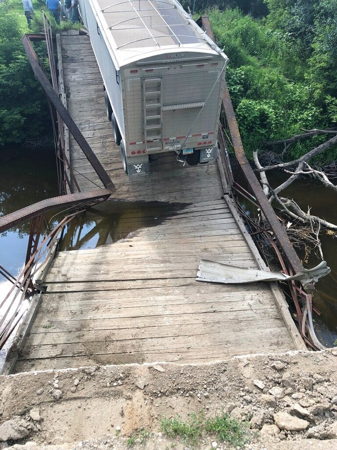 This undated photo provided by Grand Forks County Sheriff's Department shows an overweight semi has caused the collapse of a small, historic bridge near Northwood, N.D.  Authorities say the semi, with a trailer load of dry beans, was traveling on the 56-foot-long, restricted-weight bridge over the Goose River Monday, July 22, 2019, when it gave way. (Grand Forks County Sheriff's Department via AP)