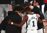 San Antonio Spurs guard Lonnie Walker IV (1) has Black Lives Matters on the back of his jersey in a huddle before an NBA basketball game against the Sacramento Kings, Friday, July 31, 2020, in Lake Buena Vista, Fla. (Kim Klement/Pool Photo via AP)