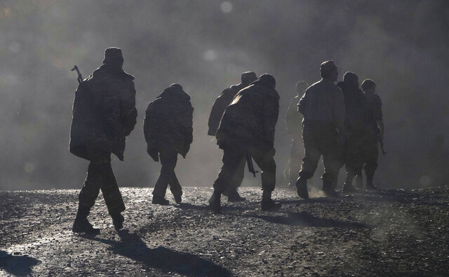 Ethnic Armenian soldiers walk along the road near the border between Nagorno-Karabakh and Armenia, Sunday, Nov. 8, 2020. Azerbaijan's president says forces have taken control of the strategically key city of Shushi in Nagorno-Karabakh, but a Armenian Defense Ministry spokesman said on Facebook that