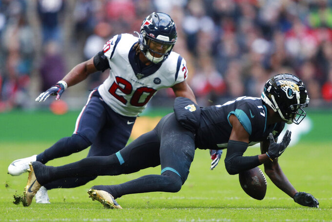 Jacksonville Jaguars wide receiver D.J. Chark (17) misses the catch agaunst Houston Texans strong safety Justin Reid (20) during the first half of an NFL football game at Wembley Stadium, Sunday, Nov. 3, 2019, in London. (AP Photo/Ian Walton)