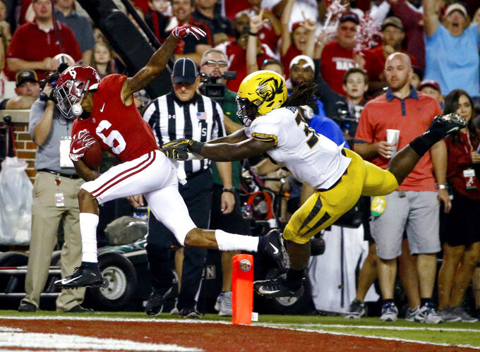 Alabama wide receiver DeVonta Smith (6) scores a touchdown as Missouri linebacker Nick Bolton (32) defends during the first half of an NCAA college football game Saturday, Oct. 13, 2018, in Tuscaloosa, Ala. (AP Photo/Butch Dill)