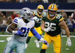 Dallas Cowboys running back Ezekiel Elliott (21) carries the ball as Green Bay Packers defensive tackle Tyler Lancaster (95) pursues in the first half of an NFL football game in Arlington, Texas, Sunday, Oct. 6, 2019. (AP Photo/Michael Ainsworth)