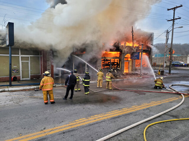 In this photo provided by Gregg Sweeten of McDonald County Emergency Management, firefighters from Noel, Pineville, Anderson, and Southwest City fire departments battle a blaze that destroyed a grocery store and a mosque that were gathering spots for immigrants, Monday, Dec. 28, 2020, in Noel, Mo. (Gregg Sweeten/McDonald County Emergency Management via AP)