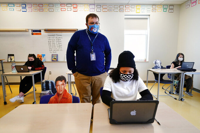 Social studies teacher Logan Landry looks over the shoulder of seventh grader Simone Moore as she works on a project while seated next to a cutout of Elvis Presley at the Bruce M. Whittier Middle School, Friday, Jan. 29, 2021, in Poland, Maine. With instruction time reduced as much as half by the coronavirus pandemic, many of the nation's middle school and high school teachers have given up on covering all the material normally included in their classes and instead are cutting lessons. Landry, put up cardboard cutouts to keep up social distancing, where instruction time has been cut in half by the hybrid model.(AP Photo/Robert F. Bukaty)