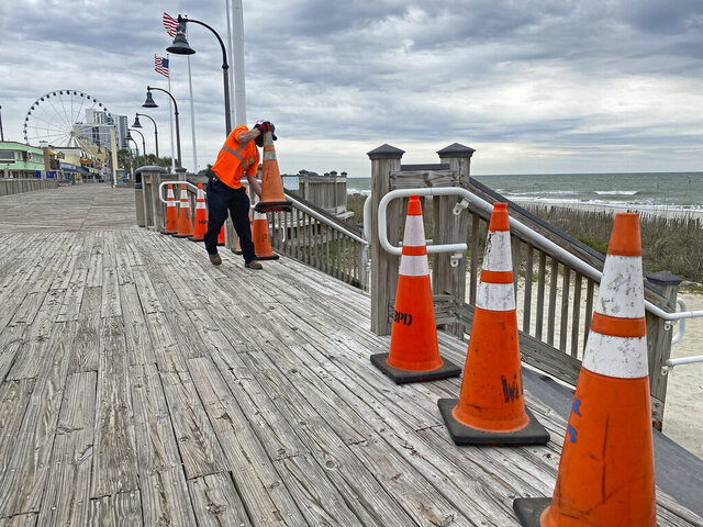 A city worker places cones to block a beach entrance along the Myrtle Beach boardwalk, Tuesday, March 31, 2020, in Myrtle Beach, S.C. Myrtle Beach Public Works crews were closing down public beach access points following South Carolina Gov. Henry McMaster's order to close access to beaches and public waterways amid the coronavirus threat. (Jason Lee/The Sun News via AP)